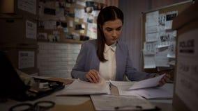 Investigador fêmea trabalhador que tenta encontrar o indício à solução da extorsão, lei fotografia de stock royalty free