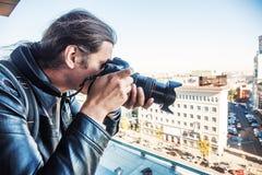 Investigador ou detetive privado ou repórter ou paparazzi que tomam a foto do balcão da construção com câmera profissional imagem de stock royalty free
