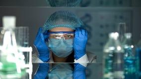 Investigador que pone en las lentes protectoras antes de trabajar con los agentes qu?micos imagen de archivo