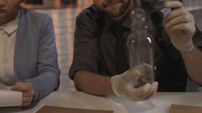 Investigador que toma huellas dactilares de la botella de las pruebas que trabaja al colega femenino almacen de metraje de vídeo