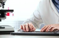 Investigador que trabaja en el ordenador Imagen de archivo libre de regalías
