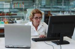 Investigador que trabaja en los ordenadores Fotografía de archivo libre de regalías