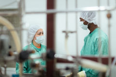 Investigadores que controlan el equipo en la industria de Biotech Fotos de archivo libres de regalías