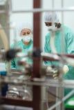 Investigadores que controlan el equipo en la industria de Biotech Imagen de archivo libre de regalías