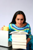 Investigate. Digital photo of a woman studying, researching in books and internet Royalty Free Stock Photos