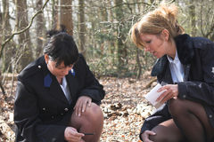 Investigating a crime scene. Two female police officers bend over in the forest to investigate a crime scene Stock Photo