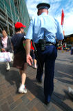 Investigation. Cop in blue uniform arresting or investigating a young man, picture is motion blurred Stock Images