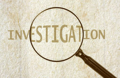 Investigation. Magnifying glass highlighting the word INVESTIGATION, over grunge aged paper Royalty Free Stock Photos