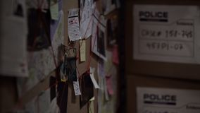 Investigation board with pinned photos, newspapers and notes, solving crime. Stock photo stock image