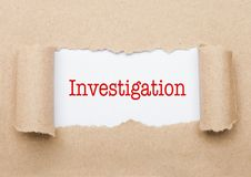 Investigation text appearing behind brown paper. Investigation concept text appearing behind torn brown paper envelope stock photos