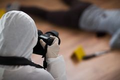 Criminalist photographing dead body at crime scene. Investigation, forensic examination and people concept - criminalist with camera photographing dead female Royalty Free Stock Photos