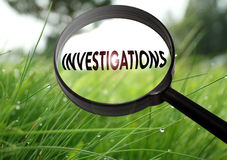 Investigations. Magnifying glass with the word investigations on grass background. Selective focus Royalty Free Stock Photography