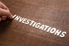 Investigations Wood Word. Hand arrange wood letters as Investigations word Royalty Free Stock Photos