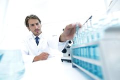Chemist looking at test-tubes with blue liquids Stock Images