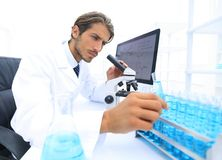 Chemist looking at test-tubes with blue liquids. The investigator checks the test tubes with a blue liquid Royalty Free Stock Image