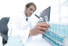 Chemist looking at test-tubes with blue liquids. The investigator checks the test tubes with a blue liquid Stock Photos