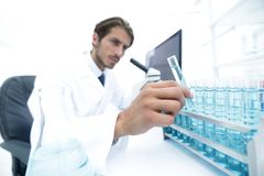 Chemist looking at test-tubes with blue liquids. The investigator checks the test tubes with a blue liquid Royalty Free Stock Photography