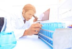 Chemist looking at test-tubes with blue liquids. The investigator checks the test tubes with a blue liquid Stock Images