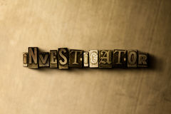 INVESTIGATOR - close-up of grungy vintage typeset word on metal backdrop Royalty Free Stock Image