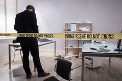 Investigator Collecting Evidence In Office. Behind Yellow Crime Scene Tape royalty free stock image
