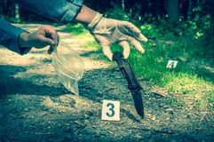 Investigator collects evidence - crime scene investigation. Investigator collects evidence army knife - crime scene investigation - retro style royalty free stock image