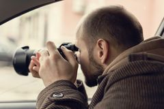 Investigator or private detective or reporter or paparazzi sitting in car and taking photo with professional camera. Toned stock photo