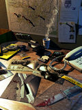 Investigator's desk. Several objects on a table, policeman badge, gun, a phone and photographies and evidences of crimes. On a board, a city map  and police Stock Images