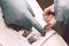 The investigator takes fingerprints from the suspect in the crime. Investigation is a crime. Crime. The investigator takes fingerprints from the suspect in the Stock Photography