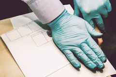 The investigator takes fingerprints from the suspect in the crime. Investigation is a crime. Crime. Stock Images