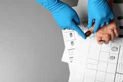 Investigator taking fingerprints of suspect on table, closeup. Space for text. Investigator taking fingerprints of suspect on grey table, closeup. Space for text stock image