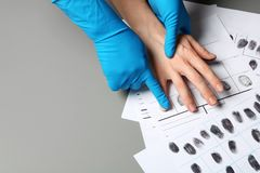 Investigator taking fingerprints of suspect on grey table, closeup. Space for text royalty free stock photos