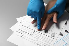 Investigator taking fingerprints of suspect on grey, closeup. Space for text. Investigator taking fingerprints of suspect on grey table, closeup. Space for text royalty free stock image