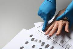 Investigator taking fingerprints of suspect on grey table, closeup. stock photos