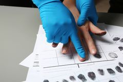 Investigator taking fingerprints of suspect on table. Closeup stock photos