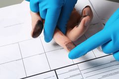 Investigator taking fingerprints of suspect on table. Closeup stock images