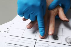 Investigator taking fingerprints of suspect on table. Closeup stock image