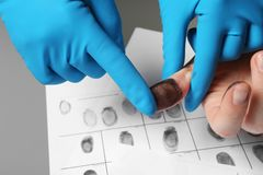 Investigator taking fingerprints of suspect on table. Closeup royalty free stock photography