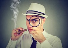 Investigator young man looking through magnifying glass. Investigator man with hat and cigar looking through magnifying glass royalty free stock photo