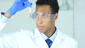 Investigue al científico, doctor que mira la solución roja en tubo de ensayo en laboratorio almacen de video