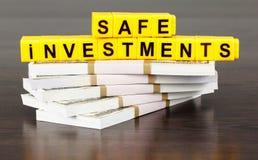 Investimenti sicuri concetto, parola fatta per lettera, pila di banconote in dollari Immagini Stock Libere da Diritti