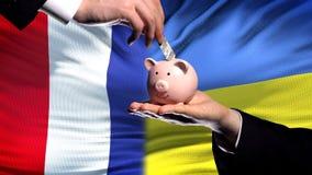 Investimento de França em Ucrânia, mão que põe o dinheiro no piggybank sobre o fundo da bandeira fotos de stock royalty free