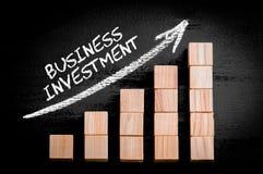 Investimento empresarial das palavras na seta de ascensão acima do gráfico de barra Fotografia de Stock