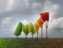 Investing during Autumn. Season as a group of trees shaped as a financial profit arrow that are changing leaf color as a finance symbol of aging investment and Stock Images