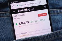 investing Com-website met de index van CAC 40 FCHI op smartphone wordt getoond in jeanszak die wordt verborgen royalty-vrije stock fotografie