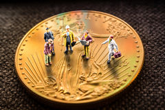 Investing in gold, precious metals. Closeup of golden american eagle coin with a reflection of close digital device and miniature business men figurines having a Royalty Free Stock Images