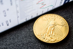 Investing in golden coins. Closeup of golden american eagle coin with a chart reflection on close digital device with green and red bars royalty free stock photos