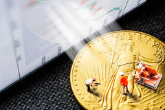 Investing in golden coins. Closeup of golden american eagle coin with a chart reflection on close digital device with green and red bars and miniature figurines royalty free stock photo