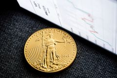 Investing in golden coins. Closeup of golden american eagle coin with a chart reflection on close digital device with green and red bars royalty free stock images