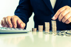Investing Money grow concept. Close up Of Businessman Hand Count and Put Money Coins To Stack Of Coins Stock Photography
