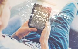 Investing in yourself with man using a tablet. In a chair stock photos